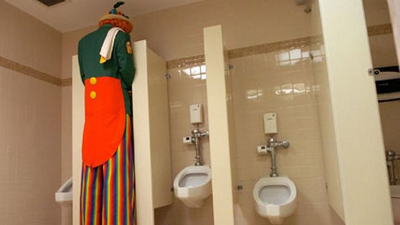Un hombre muy alto y de vestido muy colorido orinando en un baño solo para hombres