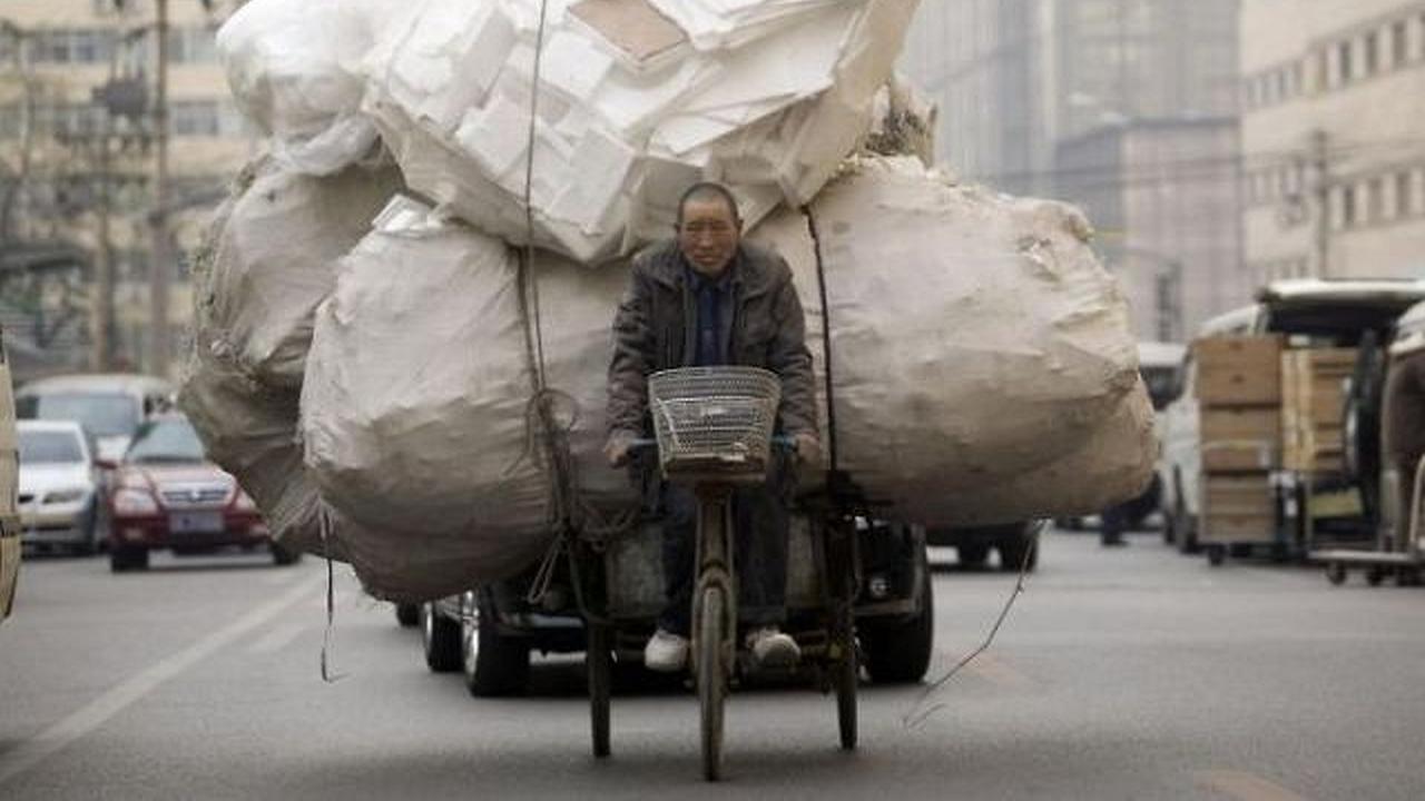 Un hombre esta arrastrando una carretica con una bicicleta en donde lleva varios costales gigantes