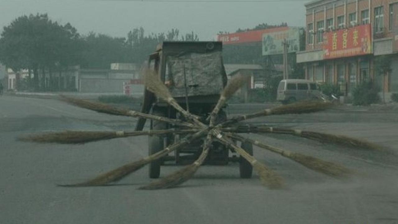 Un carrito con varias escobas viejas que son unidas por sus puntas en un mismo punto van en la parte de atras