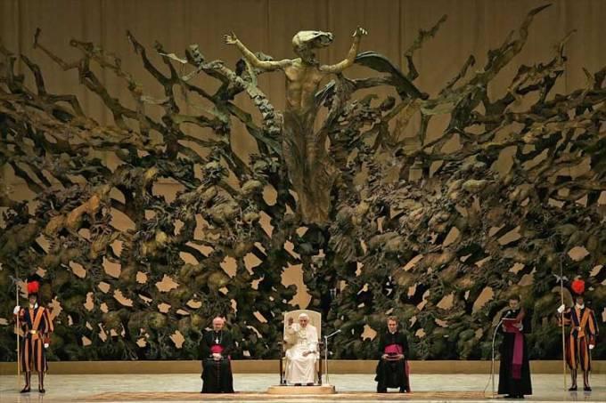 El Papa sentado y detrás una gran escultura conformada por calaberas brazoas pies, la escultura es larga y ancha y en la mitad de esta se encuentra jesus