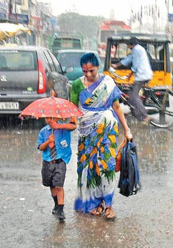 Una mujer con falda larga que camina con un niño él lleva una sombrilla y hay un fuerte aguacero