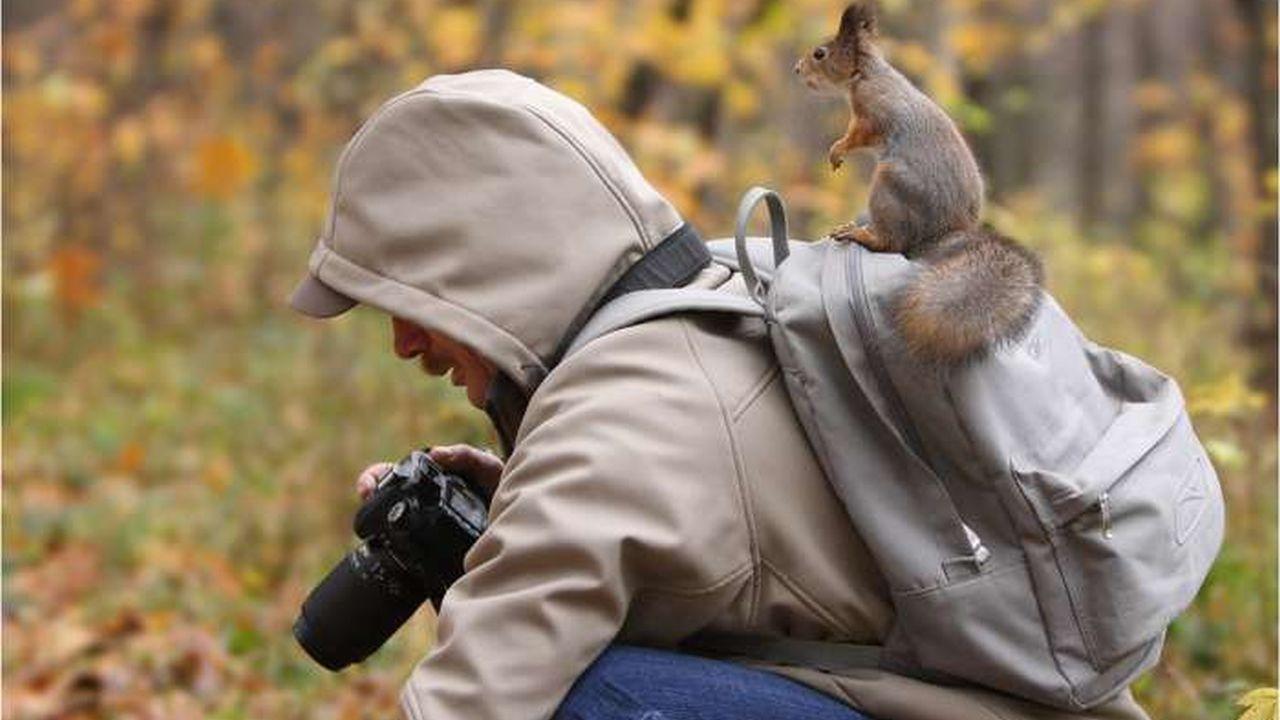 Un hombre tomando fotografías y encima de su mochila que la lleva en la espalda tiene montada una ardilla