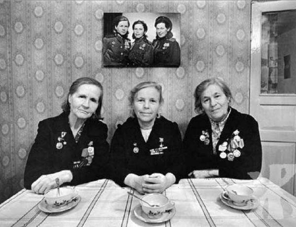 Tres mujeres con medallas sentadas en una mesa y detrás de estas un cuadro en la pared de tres mujeres jóvenes identicas