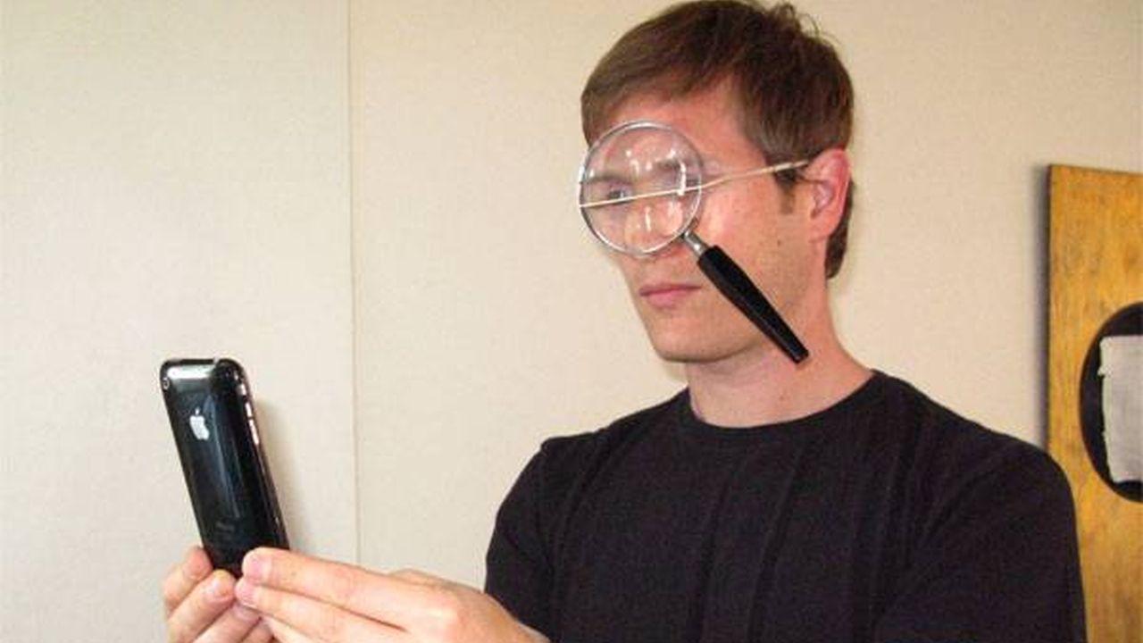 Un joven con una lupa en sus ojos mirando un celular
