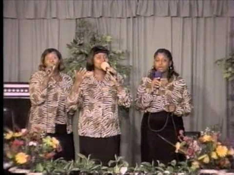 Tres mujeres afrodescendientes vestidas iguales con micrófono cantando