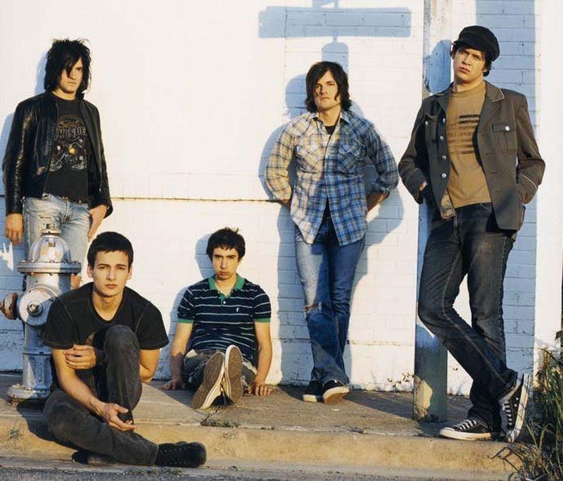 Cinco jóvenes dos sentados en el suelo y tres de pie con ropa informal