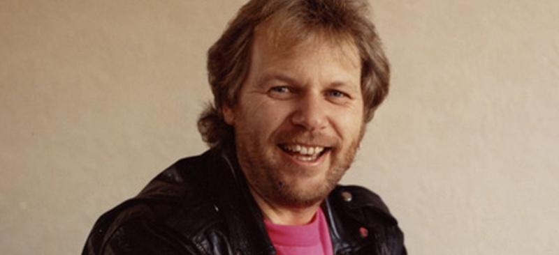 Un hombre muy sonriente rubio con chaqueta negra en cuero