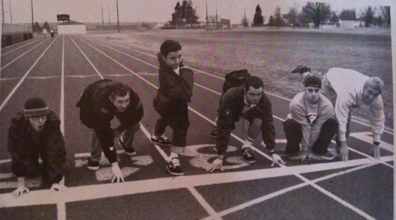 Seis jóvenes en una cancha de atletismo en diferentes posiciones listos a salir a sus marcas....