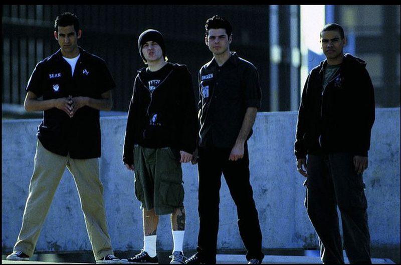 Cuatro jóvenes con ropas informales oscuras miran tranquilos