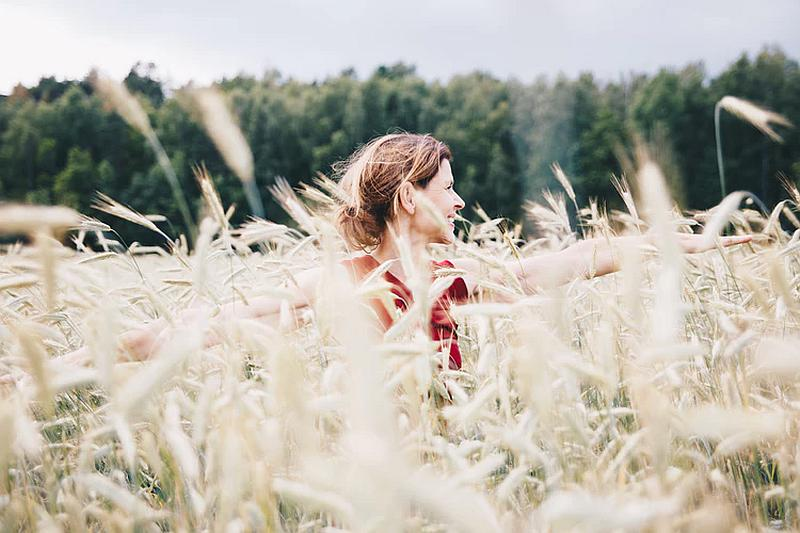 Vemos una mujer que camina entre un campo sembrado de trigo