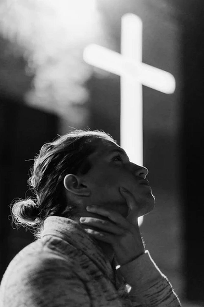 Vemos una mujer que levanta su cabeza  a lo alto y al lado vemos una cruz