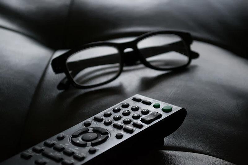 Vemos sobre una silla un control de televisión y unas gafas