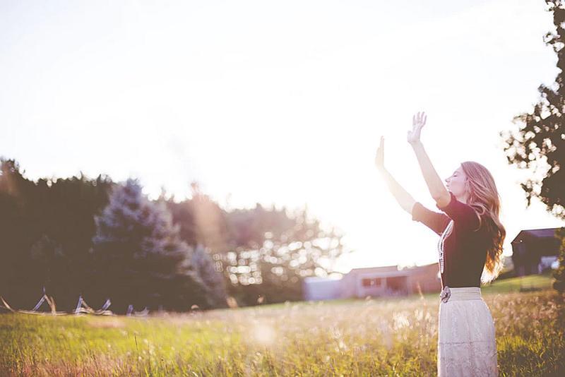 Vemos auna mujer joven que levanta sus manos en un campo verde y al fondo se ven casas y un  sitio con arboles