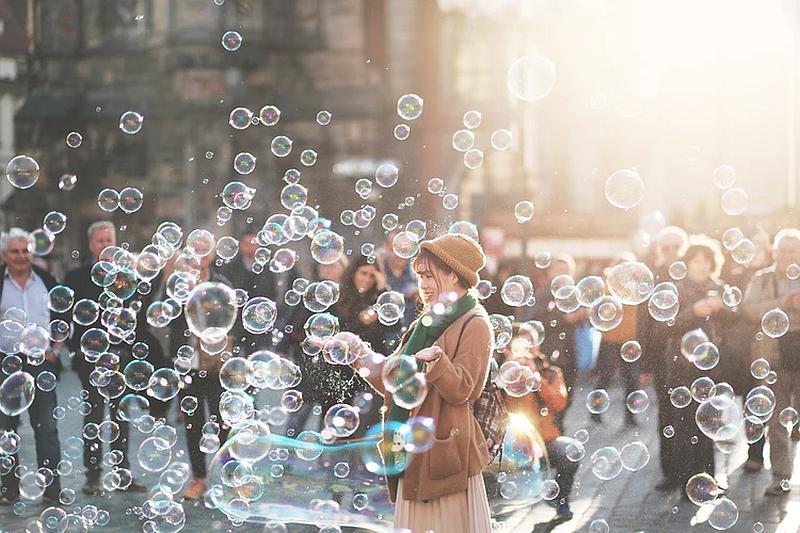 observamos auna persona que lanza miles de pompas de jabona en la calle mientras algunas personas observan