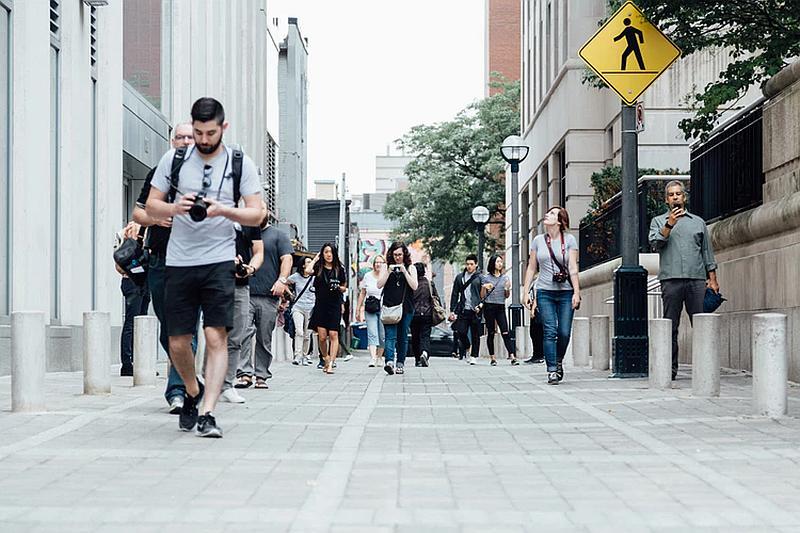 Vemos una calle peatonal con gente ambos lados que caminan rapidamente