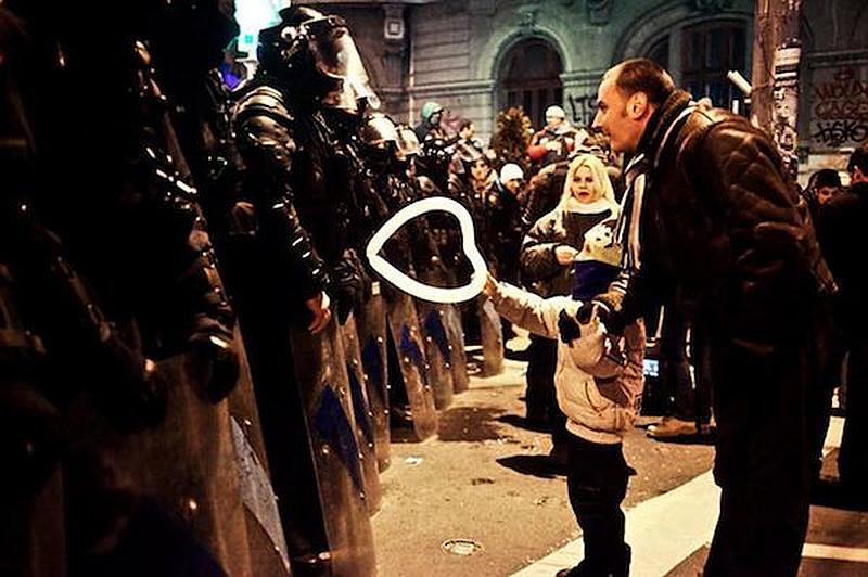 Un niño le regala un corazón a una persona de la guerra en frente de su ejercito