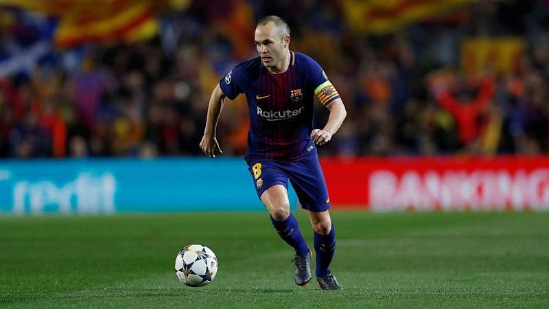 Un jugador de fútbol corre por la cancha mientras que lleva el balón a su lado