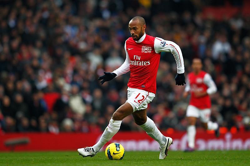 Un jugador de fútbol corre por la cancha mientras va llevando el balon