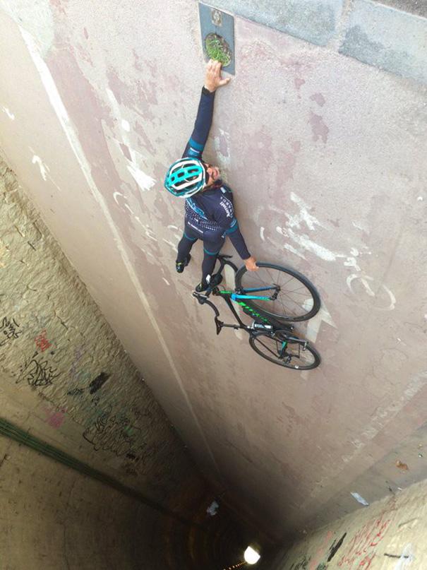 Un hombre a punto de caer al vacio y esta sosteniendo una bicicleta en el vacio...