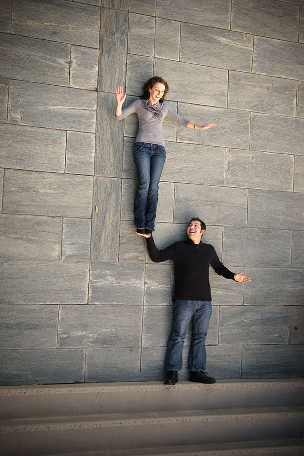 Dos personas acostadas en el piso, una esta arriba de otra, la de abajo fingiendo que la esta sosteniendo con una mano