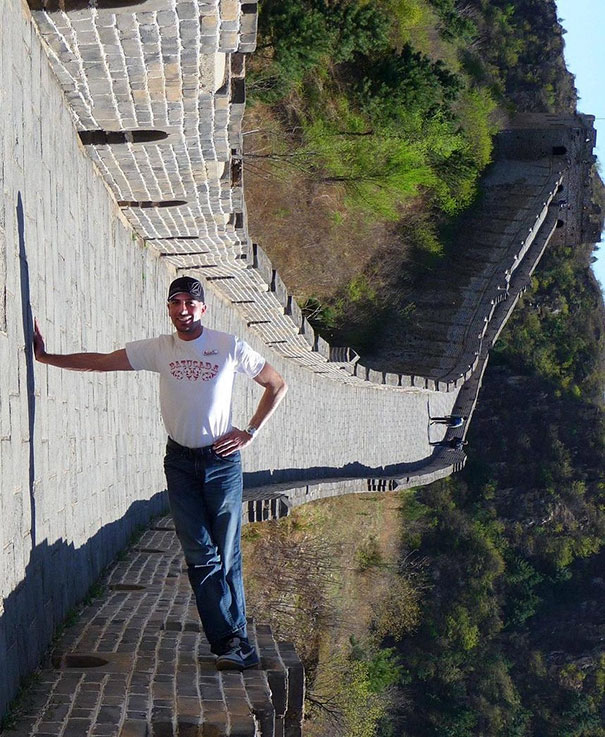 Hombre apoyandose con una mano el el piso y los pies los tiene sobre una pared
