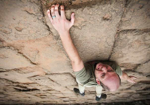 Hombre escalando una pared frente al gran vacio