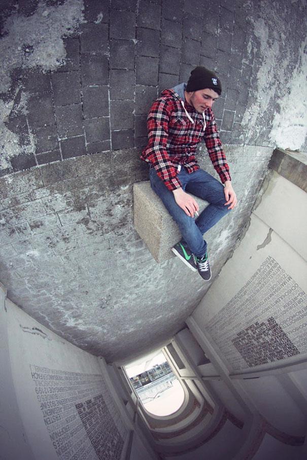 Un joven sentado en un cubito con sus pies en un vacío de un túnel