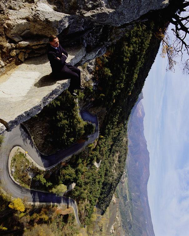 Un hombre sentado en el borde de un muro mientras observa la carretera