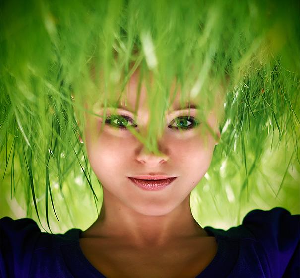 Mujer con mirada de posicion normal con su cabeza sobre el césped parece que el pelo fuera el césped