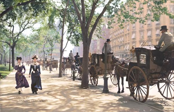 Vemos una amplia acera donde van dos mujeres con trajes de época pasada también en la calle hay muchos coches de tracción animal