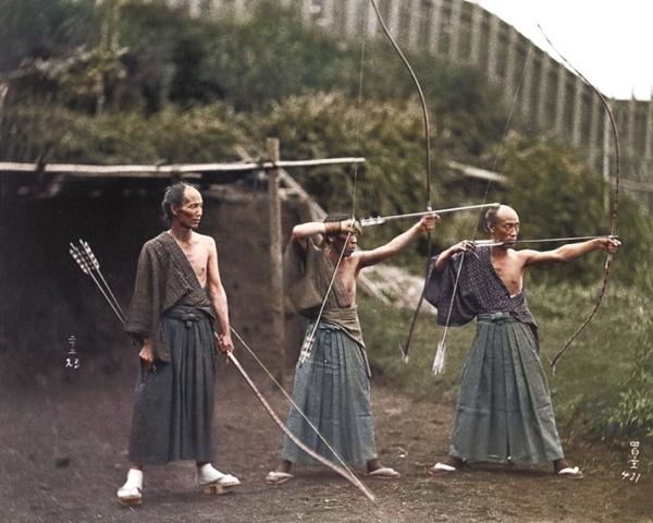 Vemos tres hombres con arcos y flechas mirando al  fondo tienen la cabeza mitas rapada en la otra mitad tienen cabello tambien usan unos largos faldones