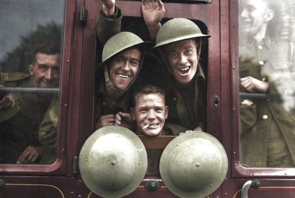 Vemos soldados sonrientes a través  del vidrio de un carro antiguo llevan cascos redondos en color verde militar