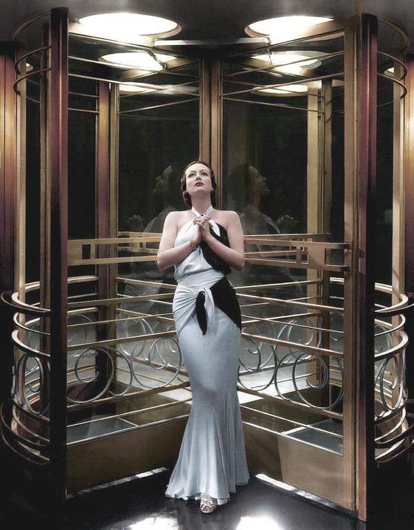 Vemos a una mujer alta rubia en la entrada de un edificio vestida elegantemente su vestido blanco con negro y largos guantes cubren  hasta muy arriba sus brazos