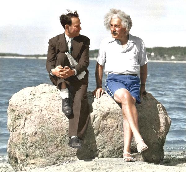 Vemos a dos hombres en una playa uno con traje entero y el oto con atuendo playero al lado el mar