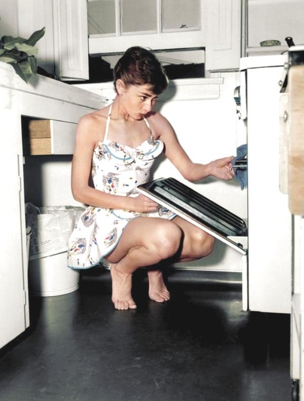mujer en cuclillas descalza con vestido florido abre un horno y observa lo que tiene adentro
