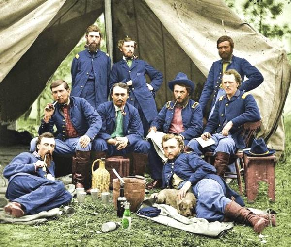 Nueve hombres y un perro celebran un rato y toman vino de una garrafa estan debajo de una carpa