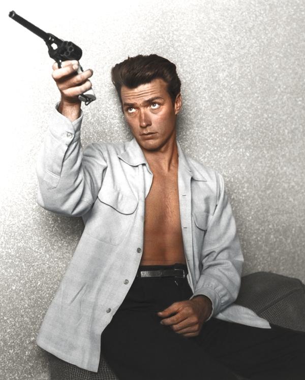 Vemos a un hombre joven con camisa blanca desabotonada aputando un arma con la mano derecha el arma esta descargada