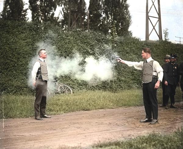Vemos varios hombres en camino donde a uno le apuntan con un arma a otro que tiene un chaleco antibalas se ve muchos arboles alrededor