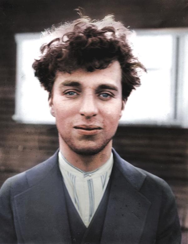 Vemos a un hombre joven con pelo crespo desordenado con ojos azules y  tiene vestido azul y camisa del mismo color sonrie un poco