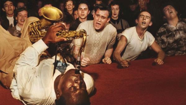 Tenemos a un hombre afrodecendiente en el suelo tocando un saxo y al lado varias personas lo escuchan y sonrien
