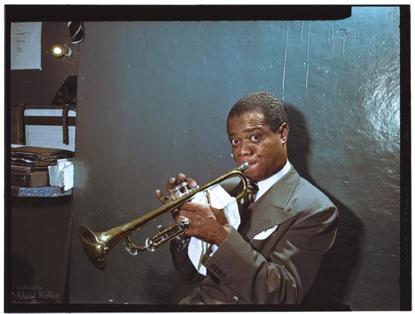 Vemos aun hombre negro joven que toca  la trompeta detrás del escenario