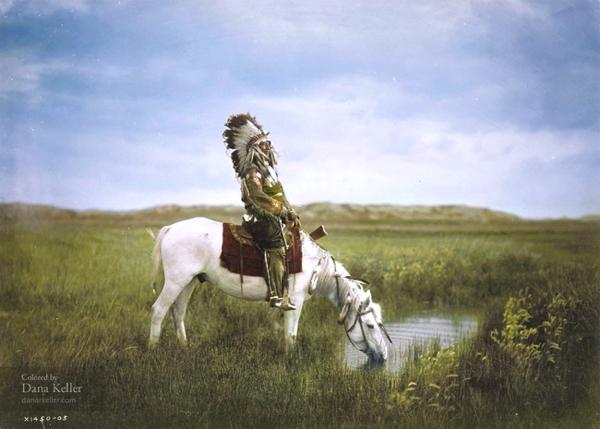 Tenemos a un jefe indio con su tocado de plumas en su cabeza va en un caballo blanco que toma agua en un riachuelo