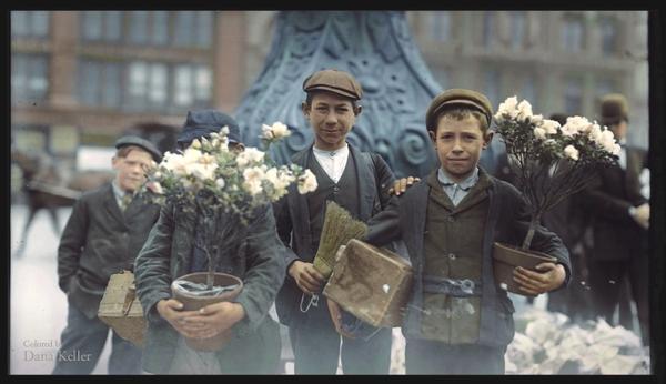Vemos a tres niños que con masetas de flores tratan de venderlas salen de un mercado