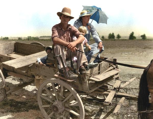 Vemos a una familia de granjeros que van en una carreta tirada por un caballo  se ve el campo polvoriento
