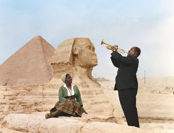 Una pareja afro en el desierto el toca la trompeta para ella al fondo la esfinge de giza