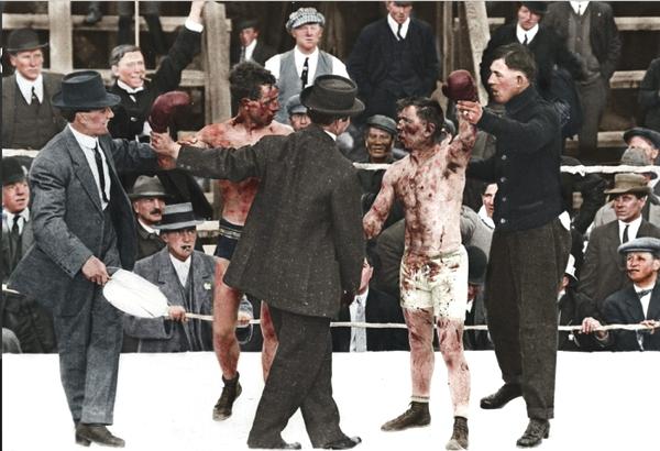 Vemos unos hombres con trajes y sombreros en un ring de boxeo un juez levanta la mano del ganador