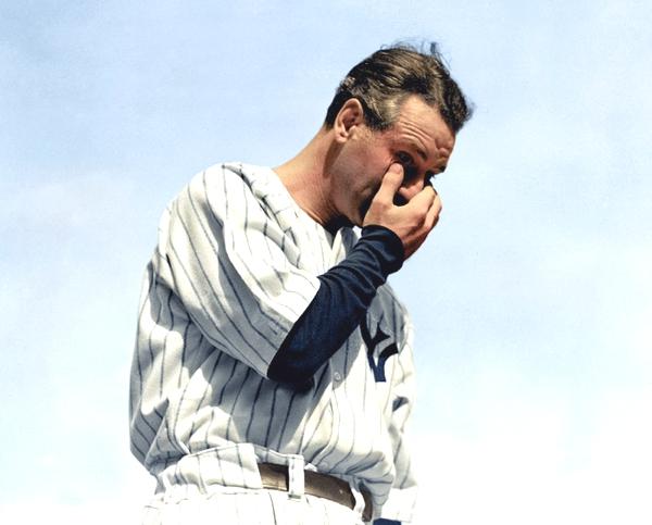 Tenemos un hombre de edad mediana con uniforme de un equipo de baseball en color azul y frotándose sus ojos