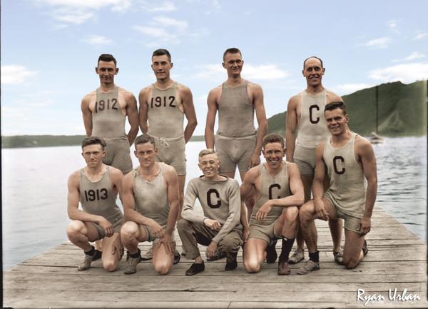 Tenemos un grupo de hombres en uniforme  de un equipo de remo sonrientes al fondo sw divisa el mar