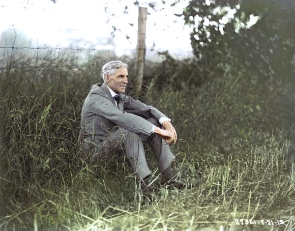 Vemos a un hombre mayor con traje y corbata sentado en un prado sonríe amigablemente