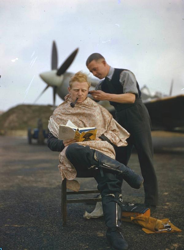 Vemos a un hombre que motila a un piloto que lee un libro tranquilamente atrás de ellos observamos un avion bombardero de la segunda guerra